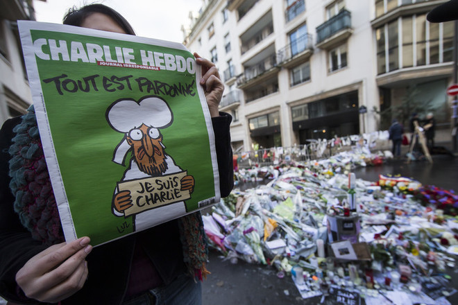 epa04559470 A woman holds the new edition of the French satirical magazine Charlie Hebdo in front of the improvised memorial on Rue Nicolas Appert, near the Charlie Hebdo headquarters, site of the 07 January attack in which 12 of the newspaper's staff were killed by two gunmen, in Paris, France, 14 January 2015. Charlie Hebdo, attacked by gunmen on 07 January, features cartoons of the prophet Muhammad in its edition, and it is published on 14 January. It will have a print run of three million, media reports said, up from an earlier announced run of one million; and far in excess of the weekly magazine's usual circulation of 60,000. EPA/IAN LANGSDON